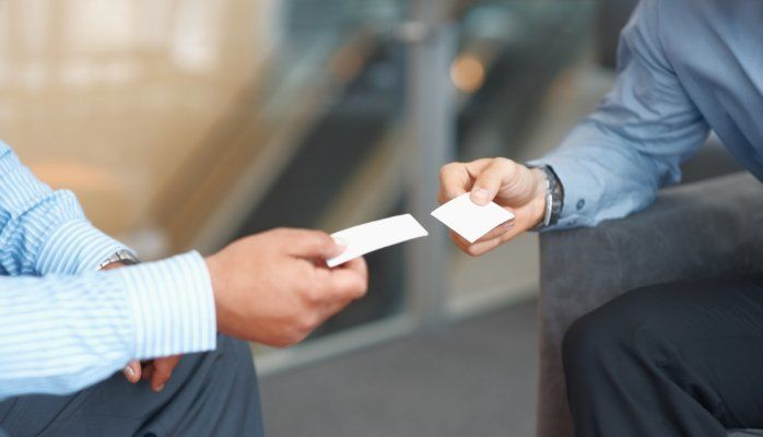 Two professionals exchanging business cards